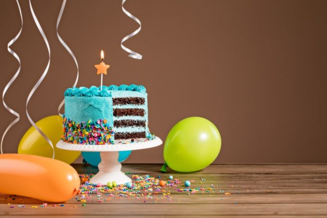 Blue birthday layer cake and air balloons and ribbons photo 673x450